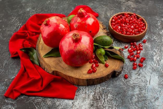 Close-up zijaanzicht granaatappels granaatappels op het bord naast de kom met granaatappelpitjes