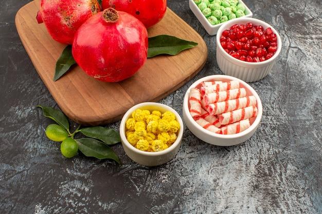 Close-up zijaanzicht granaatappels limoenen kleurrijke snoepjes drie granaatappels met bladeren op het bord