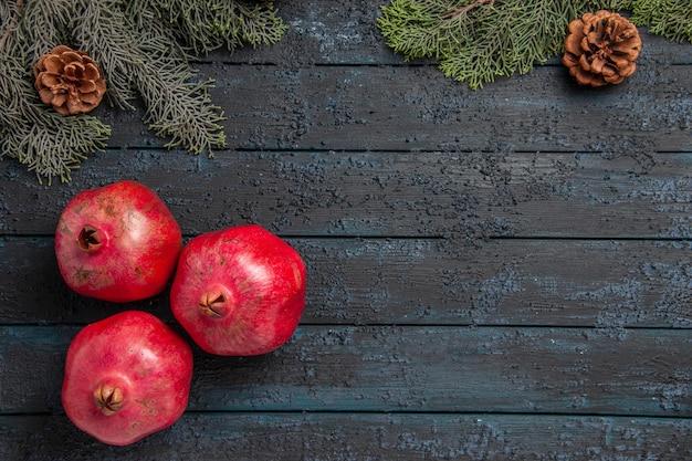 Close-up zijaanzicht granaatappels op tafel drie rode granaatappels aan de linkerkant van de tafel naast takken met kegels