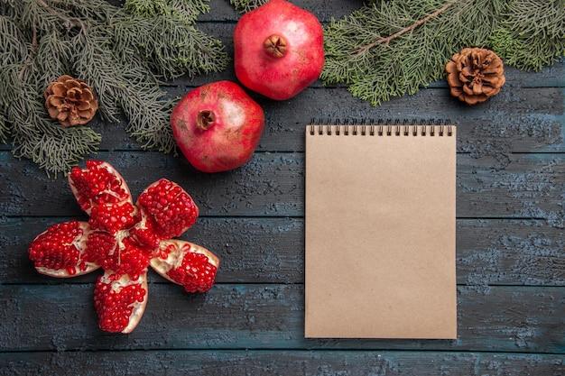 Close-up zijaanzicht granaatappels op tafel gepilde granaatappel naast twee rode granaatappels crème notitieboekje en vuren takken met kegels