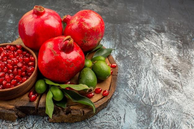 Close-up zijaanzicht granaatappels rijpe granaatappel met bladeren op de houten snijplank