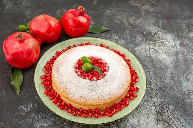 Close-up zijaanzicht granaatappels rode granaatappels en een cake met zaden van granaatappel