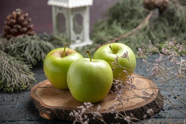 Close-up zijaanzicht groene appels smakelijk drie appels op bruin bord naast boomtakken met kegels