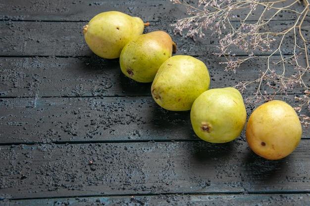 Close-up zijaanzicht groene peren vijf groene peren in het midden van donkere tafel naast de boomtakken