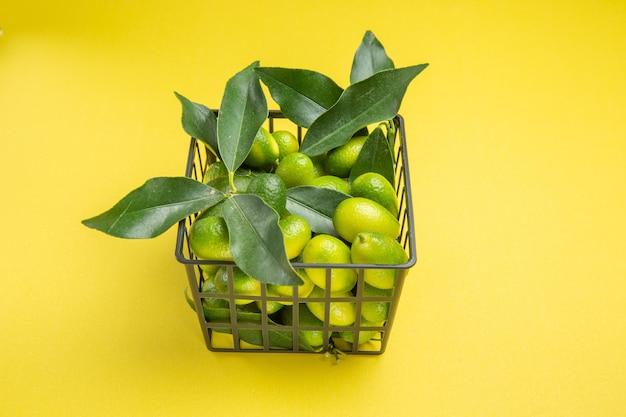 Close-up zijaanzicht groene vruchten de smakelijke groene vruchten met bladeren in de grijze mand
