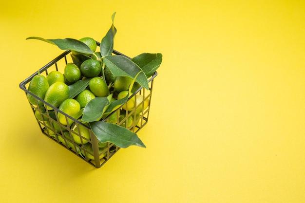 Close-up zijaanzicht groene vruchten grijze mand van de smakelijke groene vruchten met bladeren