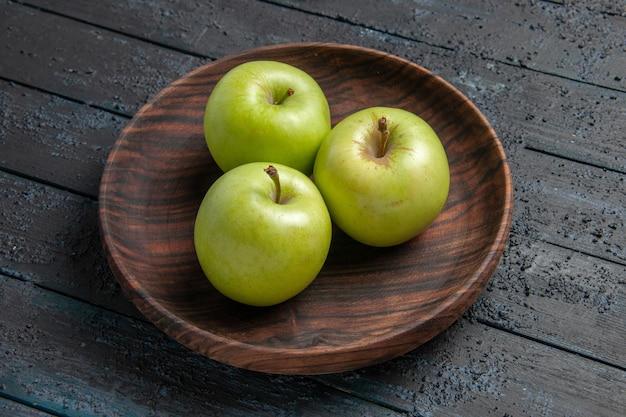 Close-up zijaanzicht kom met appels houten kom met groene appels op donkere tafel