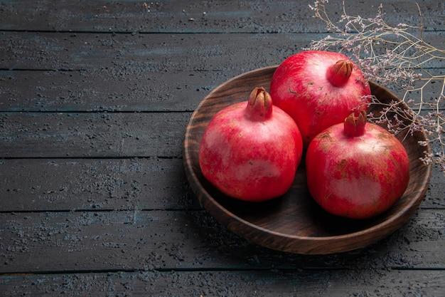 Close-up zijaanzicht kom met granaatappels drie rode granaatappels in kom naast de takken op grijze tafel