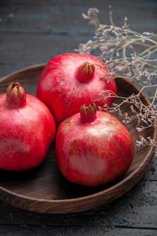 Close-up zijaanzicht kom met granaatappels drie rode granaatappels in kom naast de takken op houten tafel
