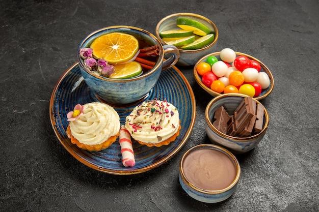 Close-up zijaanzicht kruidenthee een kopje thee met kaneel en citroen en de smakelijke cupcakes naast de kommen chocolade, schijfjes limoenchocoladecrème en kleurrijke snoepjes op tafel