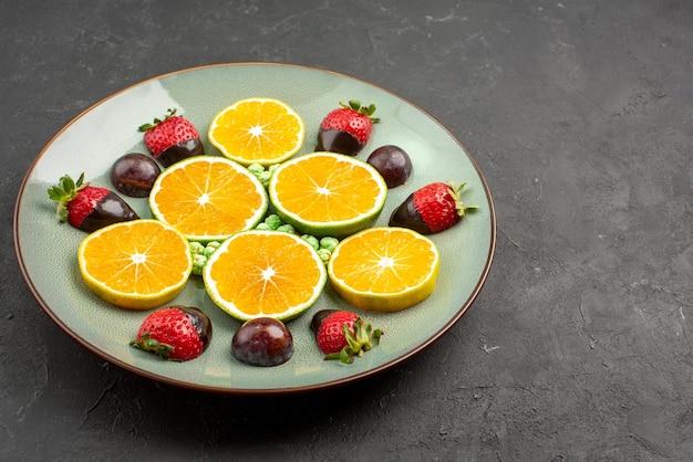 Close-up zijaanzicht met chocolade bedekte aardbei, smakelijke met chocolade bedekte aardbeigroene snoepjes en gehakte sinaasappel op plaat aan de linkerkant van donkere tafel