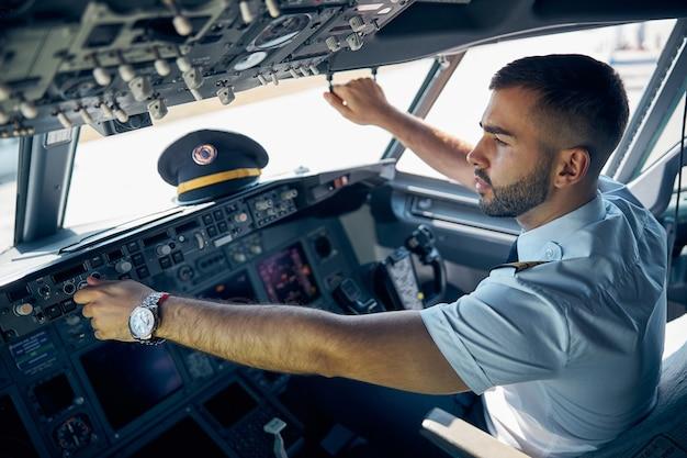 Close-up zijaanzicht portret knappe zelfverzekerde man in uniform zittend op de stoel terwijl hij het systeem van het vliegtuig controleert