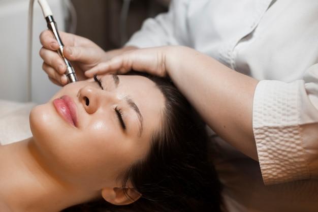 Close-up zijaanzicht portret van een leuke vrouw doet niet-invasieve microdermabrasie op haar gezicht met een dermapen door een schoonheidsspecialiste.
