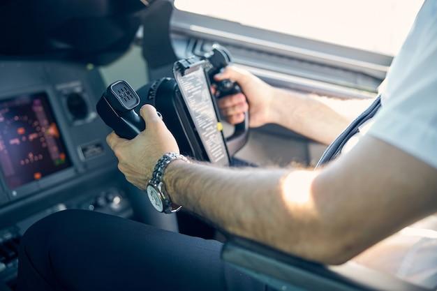 Close-up zijaanzicht portret van zelfverzekerde piloot die zich voorbereidt op de landing om te vertrekken op de luchthaven