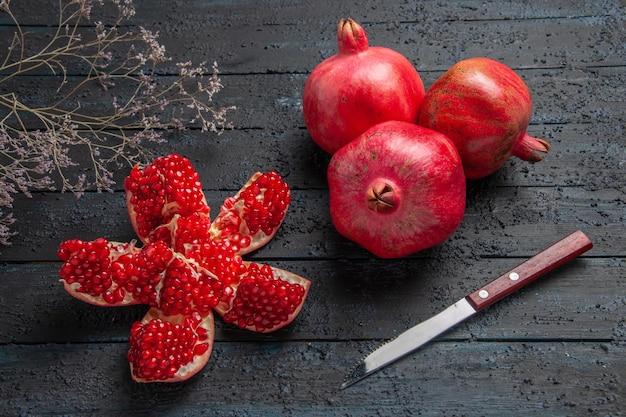 Close-up zijaanzicht rijpe granaatappels rijpe gepilde granaatappel tussen boomtakken drie granaatappels en mes op donkere achtergrond