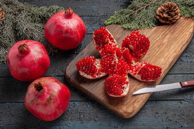 Close-up zijaanzicht rode granaatappels gepilde granaatappel op keukenbord naast takken met kegels mes en drie granaatappels op grijze tafel