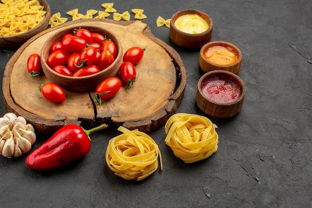 Close-up zijaanzicht smakelijke voedselpasta met drie soorten sauzen, ui, paprika en knoflook naast de kom tomaten op de houten snijplank