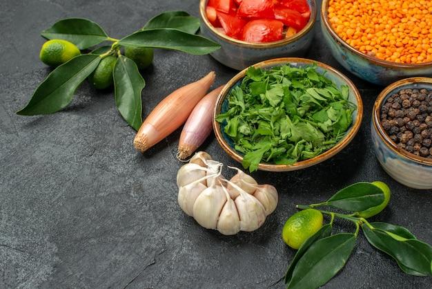Close-up zijaanzicht specerijen linzen zwarte peper kruiden uien tomaten knoflook citrusvruchten