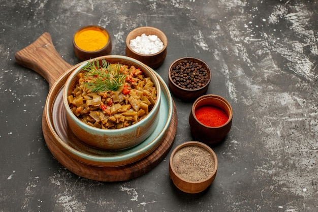 Close-up zijaanzicht tomaten en sperziebonen vijf kommen met verschillende kruiden rond de snijplank met schotel van sperziebonen en tomaten op de zwarte tafel