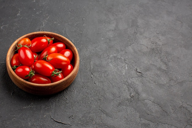 Close-up zijaanzicht tomaten houten kom met rijpe rode tomaten aan de linkerkant van de donkere tafel