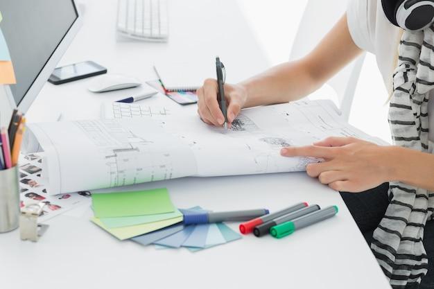 Close-up zijaanzicht van een kunstenaarstekening iets op papier met pen op het kantoor