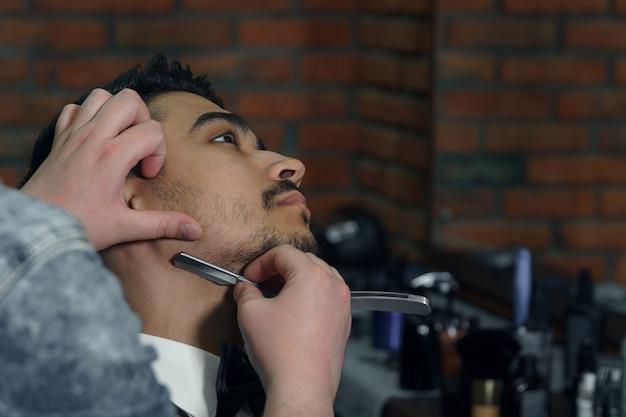 Close-up zijaanzicht van jonge, bebaarde man die baardkapsel krijgt door kapper bij kapperszaak.