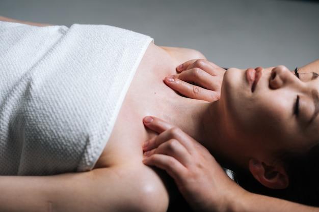 Close-up zijaanzicht van jonge vrouw die op massagetafel ligt tijdens schouder- en nekmassage