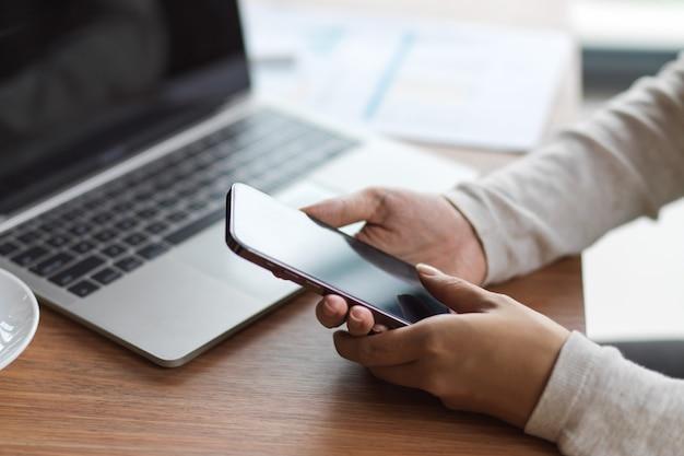 Close-up zijaanzicht van vrouwelijke handen met smartphone met laptop, papieren werken op het houten bureau wooden
