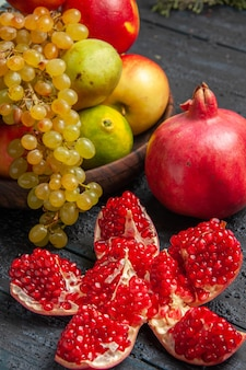 Close-up zijaanzicht vruchten in plaat bruin bord van witte en zwarte druiven limoenen peren appels naast gepilde granaatappel en takken op grijze tafel