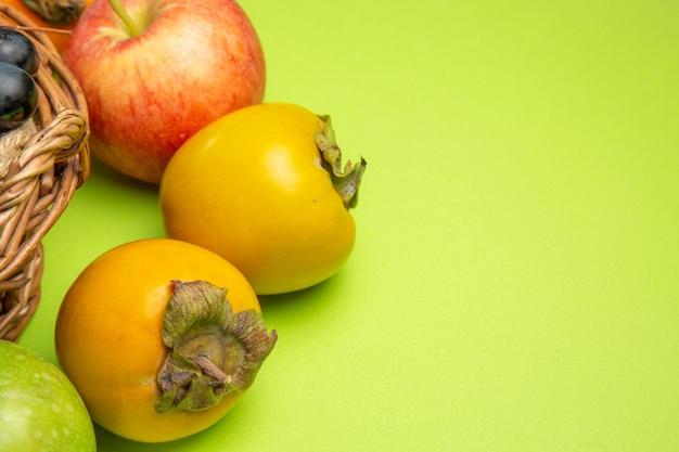 Close-up zijaanzicht vruchten kaki rode appel trossen zwarte druiven op de groene tafel