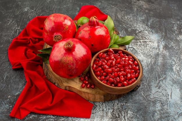 Close-up zijaanzicht vruchten rode granaatappels op de snijplank op het rode tafelkleed