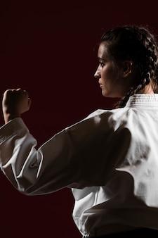 Close-up zijdelings vrouw in witte eenvormige karate