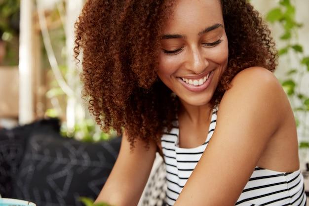 Close-up zijwaarts portret van gelukkige jonge afro-amerikaanse vrouw kijkt met verlegen uitdrukking naar beneden, nonchalant gekleed, verheugd om vrije tijd met vriend door te brengen, een aangenaam gesprek te hebben