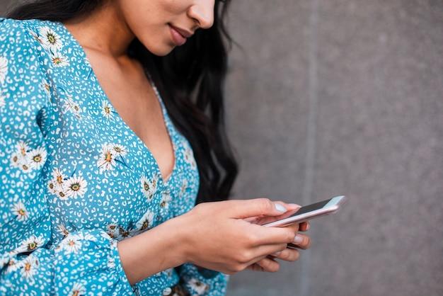 Close-up zijwaarts vrouw met behulp van haar telefoon