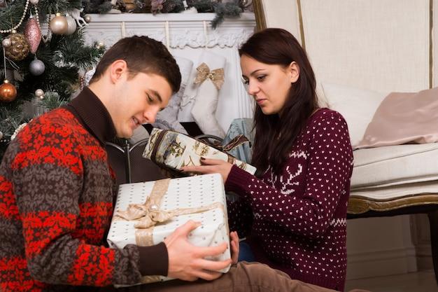 Close-up zitten jonge partners in trendy winteroutfit met kerstcadeautjes in de buurt van de kerstboom en de schoorsteenmuur.