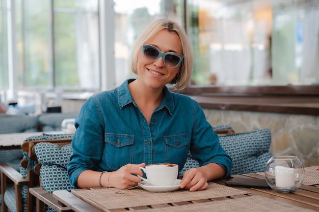 Close - up zomer portret van een jongedame meisje in modieuze zonnebril met een ochtend kopje koffie, fel blauwe stijlvolle jurk.