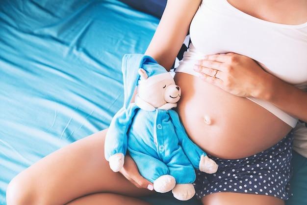 Close-up zwangere vrouw buik met teddy speelgoed beer jonge moeder verwachting van een baby
