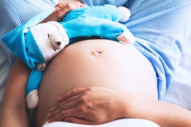 Close-up zwangere vrouw buik met teddy speelgoed beer zwangerschap concept