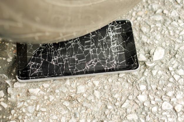 Close-up zwart mobiel telefoonongeval dat door motorfiets met glas wordt geraakt dat op weg wordt gebroken