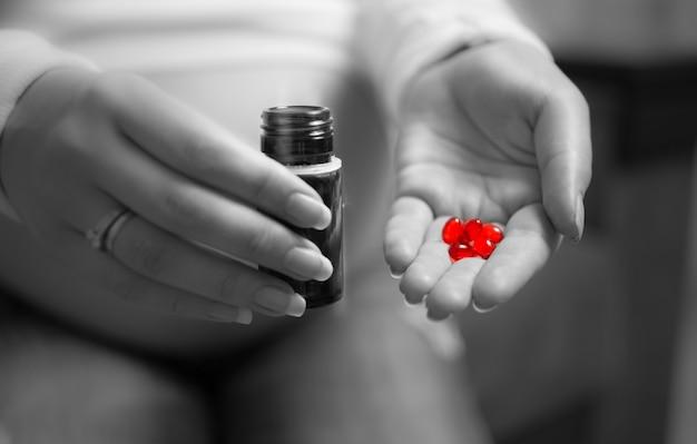 Close-up zwart-wit foto van zwangere vrouw met rode pil bij de hand?
