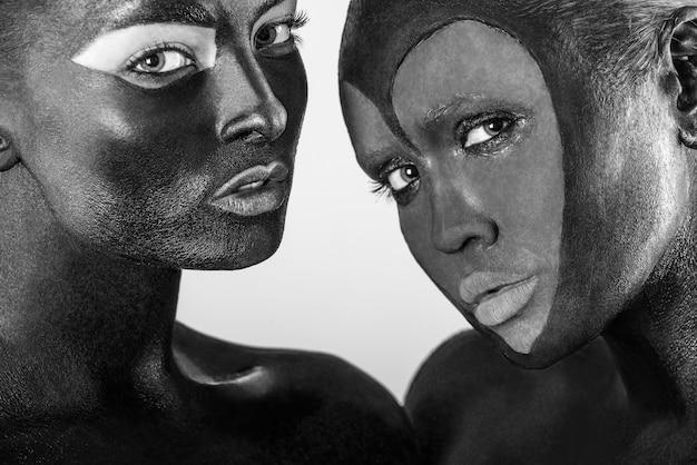 Close-up zwart-wit geschoten portret van twee mooie meisjes met lichaamskunst op het lichaam en gezicht.