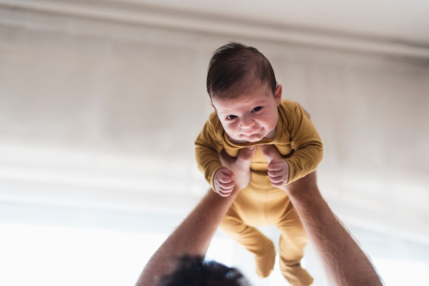 Close-upbaby die door vader wordt gesteund