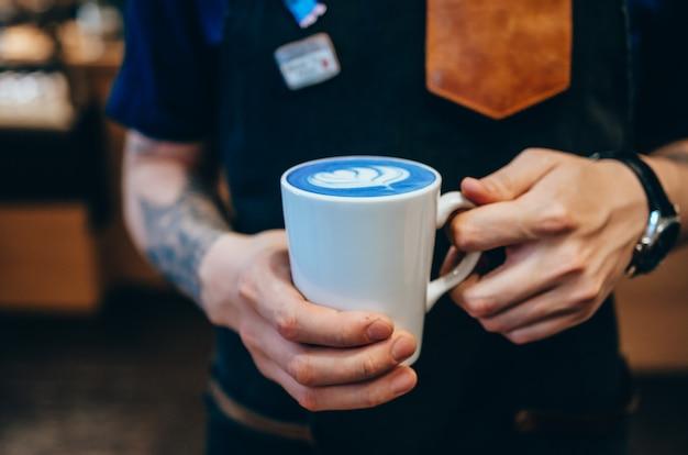 Close-upbeeld die van mannelijke handen kop van blauwe matcha latte houden