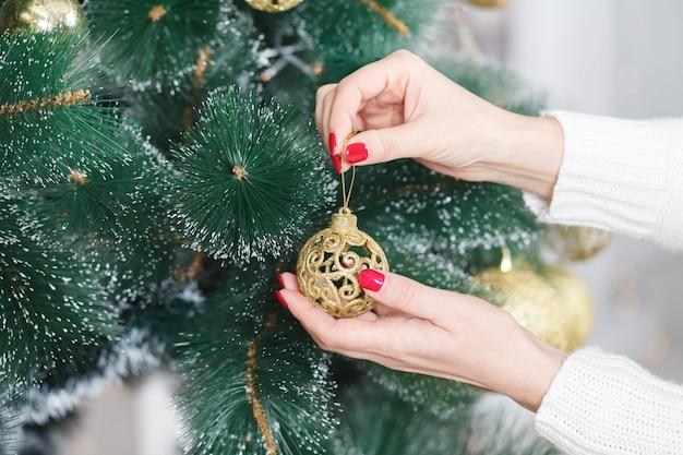 Close-upbeeld die van vrouw gouden kerstmissnuisterij houden