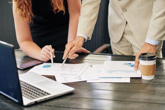 Close-upbeeld van bedrijfsmensen die statistieken van visuele activiteit tijdens vergadering bespreken