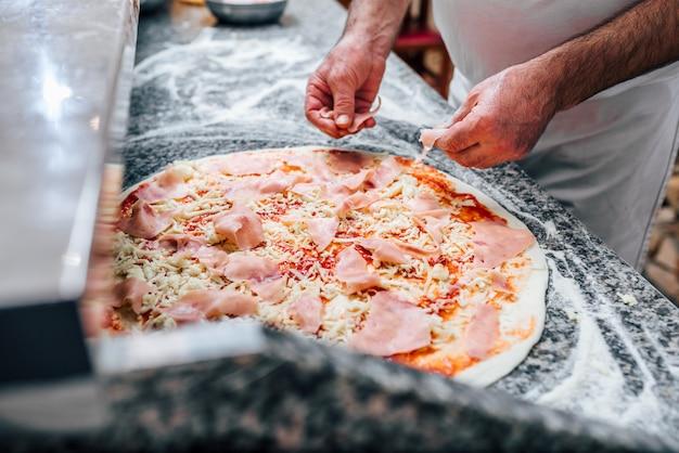 Close-upbeeld van chef-kok die de pizza maakt.