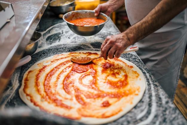 Close-upbeeld van chef-kok die pizza maakt.