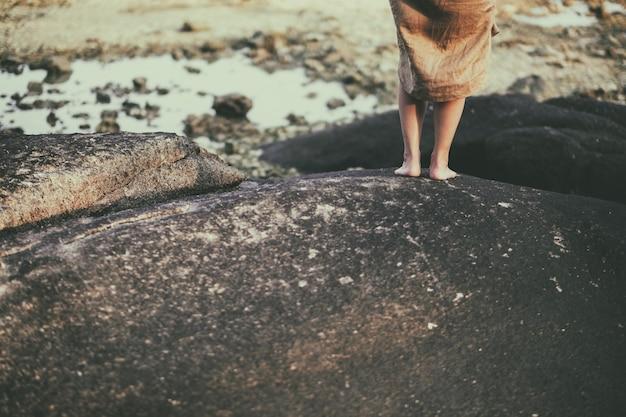 Close-upbeeld van de benen van een vrouw terwijl u op de rots aan het strand staat
