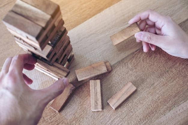Close-upbeeld van de hand van twee mensen die en het spel van het tuimeltoren houten blok spelen