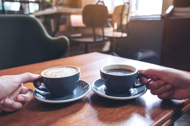 Close-upbeeld van de handen die van twee mensen koffie en hete chocoladekoppen op houten lijst in koffie houden